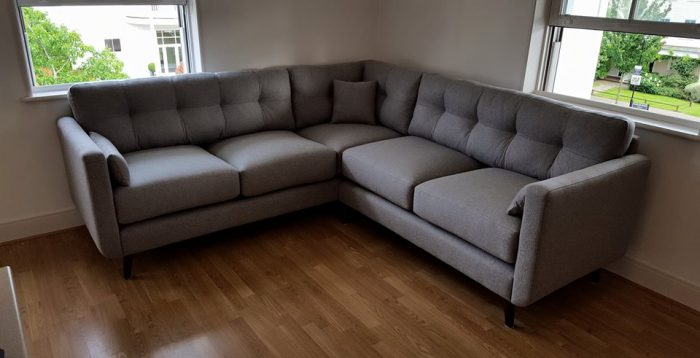 Modern corner sofa upholstered with gray fabric